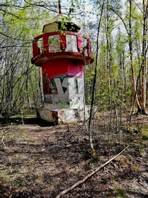 Abandoned tiny lighthouse in a forrest near a sea