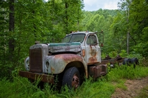 Abandoned truck on the side of a winding mountain road NCSC border