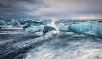 Across the ring road from the famous glacial lagoon in South Iceland is a black volcanic sand beach littered with small aquamarine icebergs The icebergs slowly drift from the lagoon out to sea where theyre then pushed onto shore by incoming waves - Jkulsr