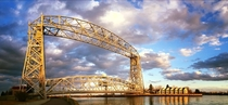Aerial Lift Bridge in Duluth MN on the western tip of Lake Superior Center span is ftm rises kyr to full height of ftm in  min Connects Park Point neighborhood to Duluth sand bar island When crossing is prevented by nautical traffic locals call it Getting