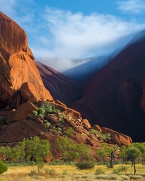 After days of heavy rain the moisture on the rock evaporated into clouds under the morning sun - Uluru NT Australia