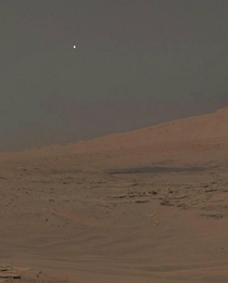 Afternoon on Mars Moon Phobos peeking over the northern limb of Mount Sharp