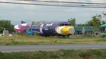 An abandoned and parted out plane on the side of the highway in Thailand for some strange reason
