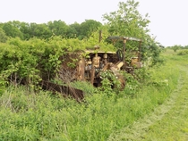 An abandoned bulldozer slowly being reclaimed by nature