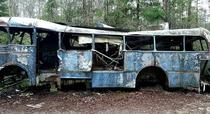 An abandoned bus in a car graveyard