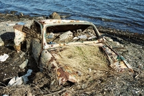 An abandoned car at low tide