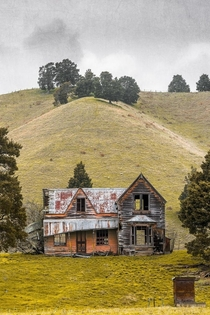 An abandoned decrepit house by a hill