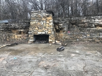 An abandoned foundation and fireplace on the side of a hill It incorporates the natural rock formations in the hill South Kansas City