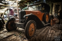 An abandoned old car among many other in a garage in the woods