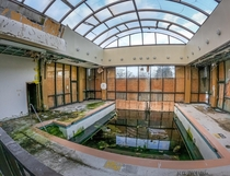 An abandoned pool at a hotel with lots of algae and moss
