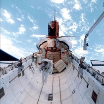 An astronaut floats in space shuttle challengers payload Bay on mission STS--C after a successful repair of solar max satellite