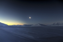 An eclipse looms over the icy peaks of Svalbard Norway in March  By Luc Jamet w links in comments