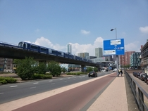 An elevated metro line three road lanes a cycle path and a sidewalk All next to each other in the city of Rotterdam Netherlands