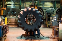 An employee works on the inside of a tire at a tire manufacturing facility in Bryan Ohio
