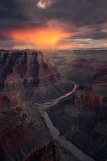 An evening storm cloud dumps rain during sunset on the South Rim of the Grand Canyon in Arizona