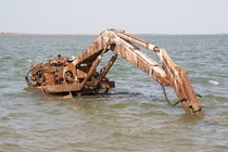 An excavator left to rust in the water near an abandoned island in Chesapeake Bay Photo by uxarvox