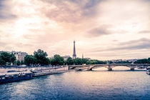 An iconic Eiffel Tower looms over the Seine on a cloudy summers day