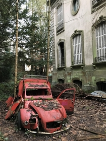An old car next to an abandoned mansion France