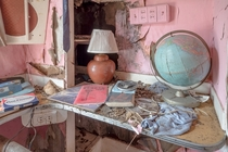An old globe and miscellaneous items on a desk in an abandoned house OC