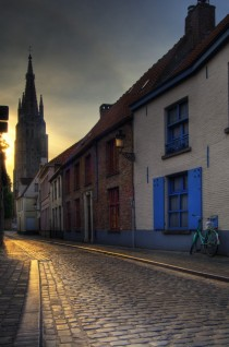 An old street in Bruges Belgium with the Church of Our Lady tower in the background