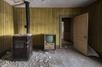 An old television next to an old furnace in an abandoned house in northeastern Ontario Canada OC