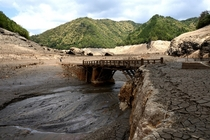An old wooden bridge that was for several decades until a few days ago was underwater at the bottom of Horai Lake reservoir of Shinshiro City Aichi Prefecture Japan