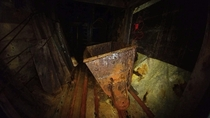 An ore cart and elevator lie abandoned far underground in the abandoned Evening Star Mine Lane County OR OC