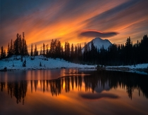 An underlit swooping lenticular cloud perfectly outlines Mt Rainier at Tipsoo Lake WA USA
