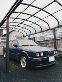 Another abandoned car in Tokyo Japan This ones a classic someone please ID the model thick layer of dust covering the top all  tires flat with BBSsa few magazines scattered in the back seat Beautiful amp timeless