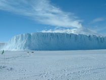 Antarcticas Barne Glacier where it meets the frozen ocean with Mt Erebus volcano smoking in the background