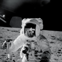 Apollo  astronaut Alan Bean holds a special environmental sample container filled with lunar soil collected during his sojourn on the lunar surface A Hasselblad camera is mounted on the chest of his spacesuit Pete Conrad who took this image is reflected i