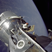Apollo  CommandService Modules nicknamed Gumdrop and Lunar Module nicknamed Spider are shown docked together as Command Module pilot David R Scott stands in the open hatch on March