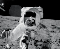 Apollo  lunar module pilot Alan Bean holds a container of lunar soil with the reflection of mission commander Charles Pete Conrad Jr visible on his visor