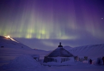 Arctic hut on the island of Spitsbergen lit by Aurora