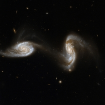 Arp  The galaxies are located very far away about  million light-years and they are in the very early stages of interacting with each other and will eventually merge into a larger galaxy Galaxies of all shapes and sizes are also visible in the background