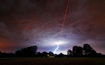 As ESO was testing the Wendelstein laser guide star unit Algu south Germany by shooting a powerful laser beam into the atmosphere one of the regions intense summer thunderstorms was approaching Credit ESOM Kornmesser