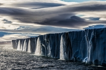 As our ship approached the massive ice cap I was shocked to see a string of waterfalls that straddled the entire expanse of the melting ice - Nordaustlandet Svalbard Norway  Photo by Paul Nicklen