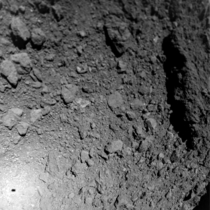 Asteroid Ryugu as seen from Hayabusas MASCOT lander Note MASCOTs shadow to the lower left and the huge boulder to the right which is tens of meters long