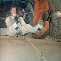 Astronaut David R Scott holds maneuvering unit while suspended in a weightless state during extravehicular activity training