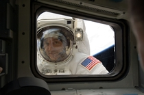 Astronaut Mike Massimino peers into Space Shuttle Atlantis aft flight deck window during STS-