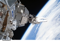 Astronaut Nicholas Patrick hangs from the cupola during the STS- missions third and final spacewalk