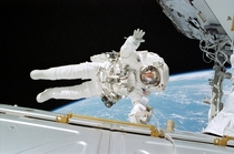 Astronaut Rex J Walheim gives a wave during an EVA during STS-