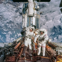 Astronauts John M Grunsfeld right and Richard M Linnehan STS- payload commander and mission specialist respectively are photographed near the giant Hubble Space Telescope temporarily hosted in the Space Shuttle Columbias cargo bay