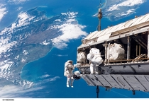 Astronauts Robert Curbeam and Christer Fuglesang performing a spacewalk over New Zealand