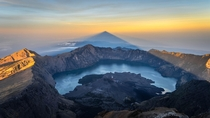 At sunrise from the summit of Rinjani Mount Lombok Island Indonesia we can contemplate the triangle-shaped shadow of the volcano over its crater lake