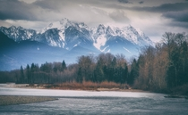 At the riverbend at The Cascade Mountains rise over the Skykomish River in Washington State US by Montana Roots