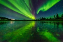 Aurora reflecting on a frozen lake near Yellowknife Northwest Territories Canada