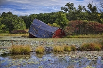 Barn falling off into a swamp Photo by Peter Stratmoen
