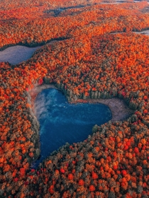 Beautiful heart shaped natural lake surrounded by fall foliage in Ontario Canada
