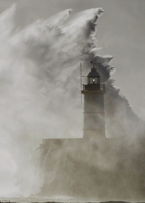 Big wave and lighthouse Newhaven England